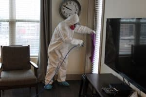a suited-up team member using sanitation equipment in an apartment.